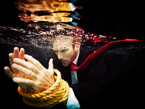 Businessman underwater with hands tied